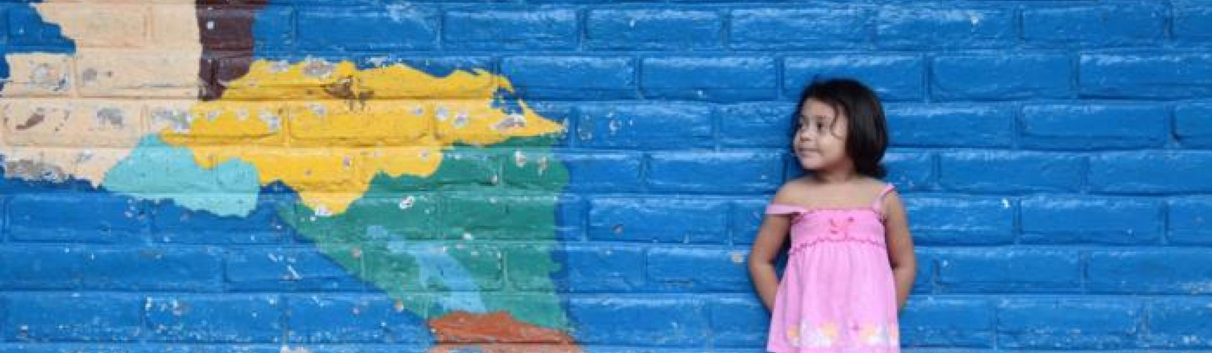 Stock photo of a girl standing against a wall in El Salvador.