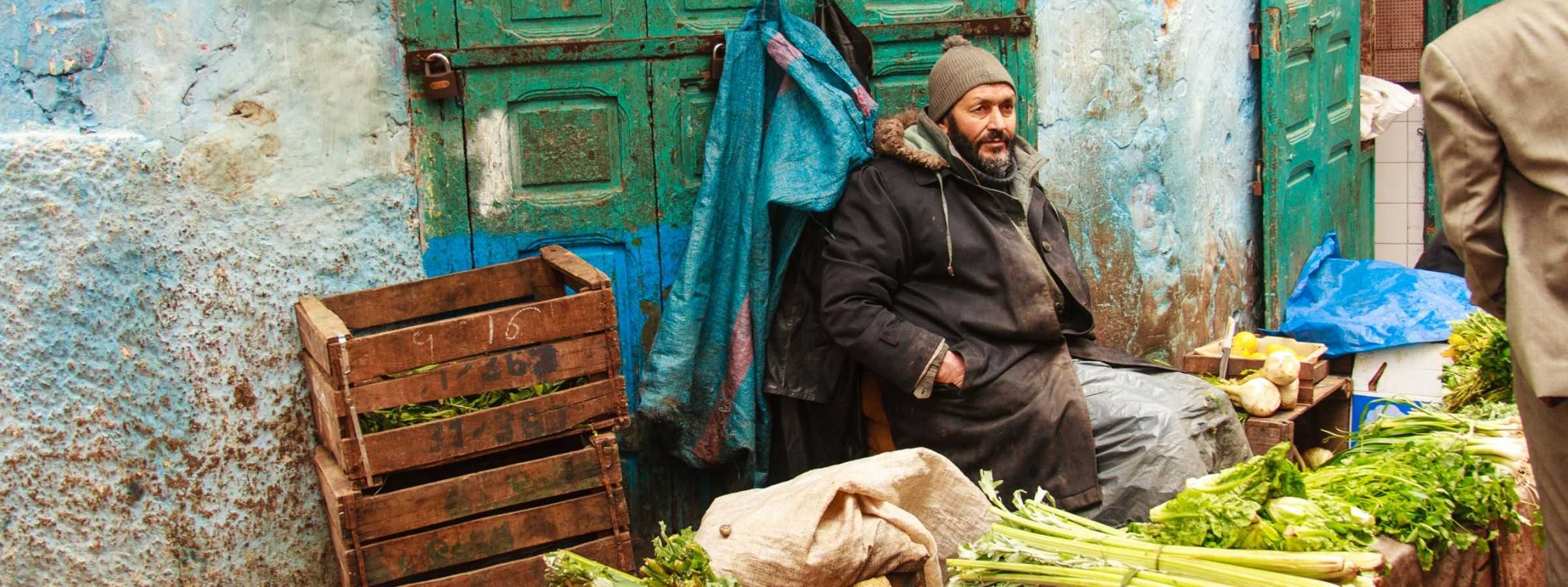 A vegetable seller sits near his produce in Rabat, Morocco